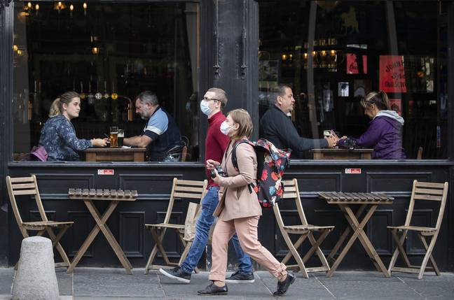 People wearing protective face masks walk past a bar in Edinburgh city centre (Credit: PA)