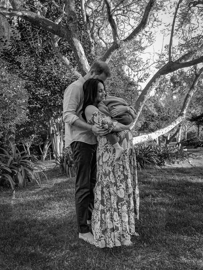 In the beautiful image, the couple can be seen standing barefoot on the grass cradling Archie (Credit: Misan Harriman)