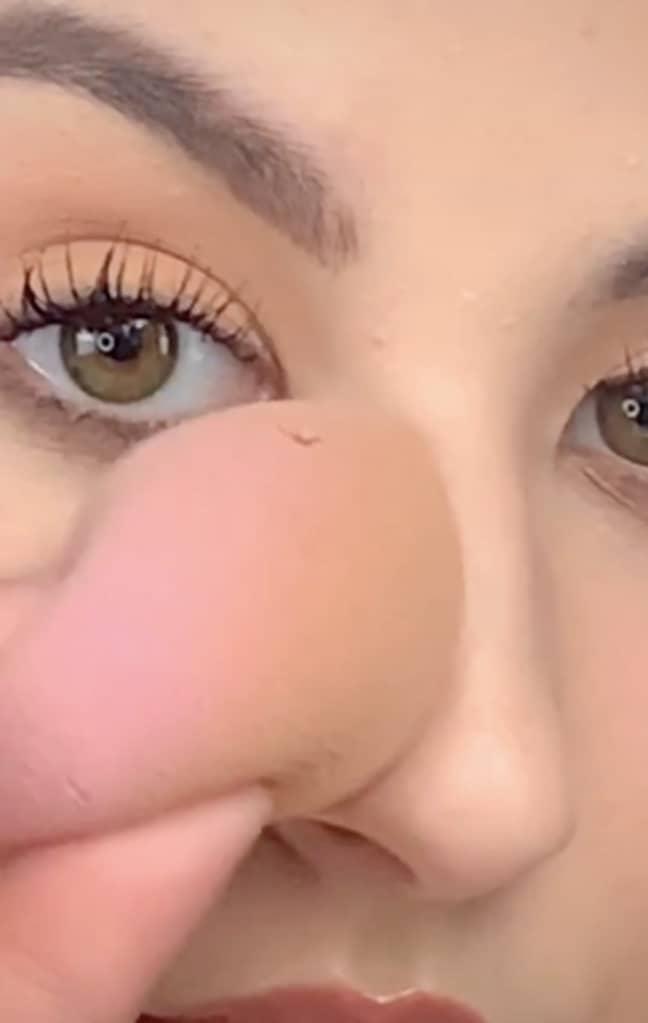 The make-up artist dabs her nose with a sponge (Credit: TikTok/@elliemakeupartist)
