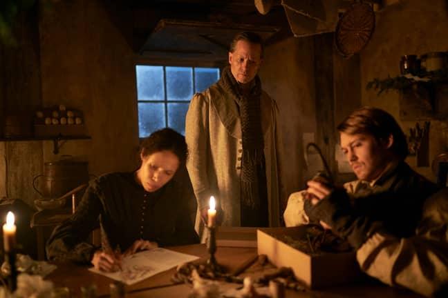 Joe Alwyn, playing Bob Cratchit, in a candlelit kitchen scene (Credit: BBC)